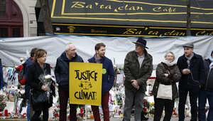 متظاهرون يشاركون في مسيرة حول التغير المناخي يتوقفون أمام قاعة الحفلات الموسيقية باتاكلان في باريس