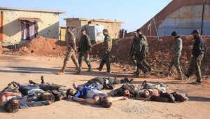 """قوات من الجيش السوري يسيرون بجانب أعضاء من """"داعش"""" قُتلوا خلال معركة وجثثهم على الأرض في قاعدة جوية بشرق محافظة حلب"""