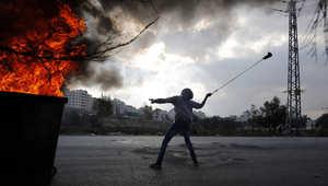 شاب فلسطيني يرمي الحجارة باتجاه الجيش الإسرائيلي