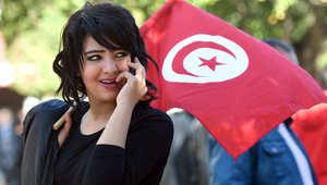 امرأة تونسية تحمل علمها الوطني خلال تجمع حاشد في 14 يناير 2016 في شارع الحبيب بورقيبة في العاصمة تونس للاحتفال بالذكرى الخامسة لثورة 2011