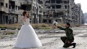بالصور.. جندي سوري وعروسه يلتقطان صور زفافهما التذكارية وسط الدمار بحلب