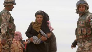 لاجئة سورية تحمل طفلاً وتمر بين عناصر الجيش الأردني بعد وصولها من سوريا