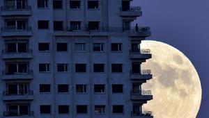 رجل يقف على شرفة مبنى في مدريد والقمر في خلفية الصورة