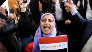 امرأة مصرية تحتفل حاملة العلم الوطني بعد تأكيد القضاء ملكية مصر لجزيرتي تيران وصنافير
