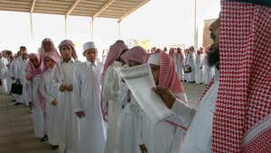 طلاب سعوديون يقفون في الصف ومعلم يتأكد من الحضور بعد أول يوم من العودة إلى المدارس بالرياض
