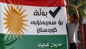 رجل كردي يعلق لافتة تحث على اجراء استفتاء حول الاستقلال في اربيل عاصمة منطقة كردستان في شمالي العراق