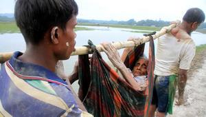 لاجئان من الروهينغا يحملان امرأة مسنة من ولاية راخين في ميانمار على طول طريق بالقرب من تكناف في بنغلاديش