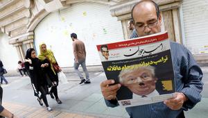 رجل إيراني يقرأ نسخة من صحيفة يومية تحمل صورة الرئيس الأمريكي دونالد ترامب