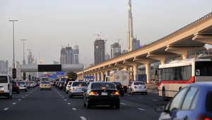 سيارات على شارع الشيخ زايد في دبي وبرج خليفة يظهر في خلفية الصورة