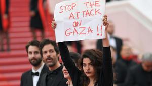 """الممثلة اللبنانية منال عيسى ترفع لافتة """"أوقفوا العدوان على غزة """" في مهرجان """"كان"""" السينمائي"""