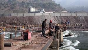 مهندس صيني يشرف على عمال يقومون ببناء جسر فوق نهر في عاصمة الشطر الباكستاني من كشمير
