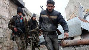 مقاتلون من المعارضة السورية ينقلون مدفعا داخل مدينة حمص