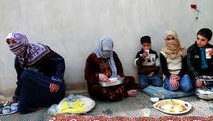 عائلة سورية تقوم بإعداد الطعام في مدينة حمص