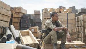 استراحة جندي إسرائيلي على أكداس عتاد قرب حدود غزة