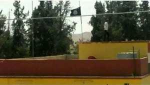 """علم """"الدولة الإسلامية"""" يرفعه عناصر داعش على مبنى السد الذي سيطروا عليه"""