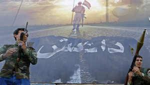 مقاتلون من التركمان يقفون أمام ملصق يحمل صورة جندي عراقي يسير منتصرا على علم ممزق لداعش