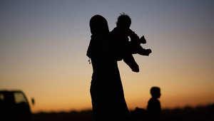 سيدة سورية تحمل طفلها بعد تجاوزها الحدود إلى تركيا