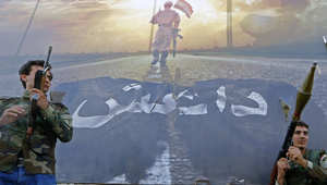 عدد من الجنود الأكراد يقفون أمام لافتة ممزقة لتنظيم داعش