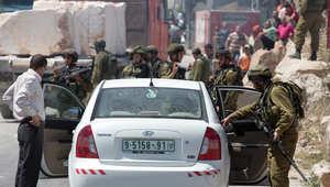 جندي إسرائيلي يفتش سيارة في الضفة الغربية