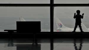 طفل ينظر اطائرة تابعة للخطوط الماليزية