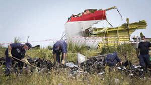 مجموعة من رجال الإنقاذ الأوكرانيين يبحثون بين حطام الطائرة الماليزية، التي كانت في طريقها من أمستردام إلى كوالالمبور