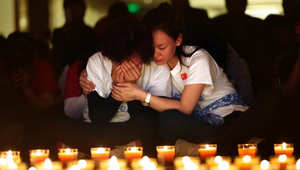 امرأة تبكي في بكين، خلال مسيرة بالشموع لضحايا الطائرة الماليزية الرحلة 370.