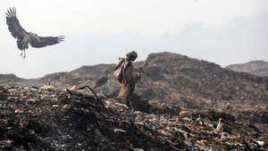 امرأة تبحث في القمامة عن مواد قابلة لإعادة التدوير في يوم الأرض في الهند.