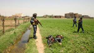 قوات الأمن العراقية تقف بالقرب من جثث أعضاء دولة العراق والشام الإسلامية