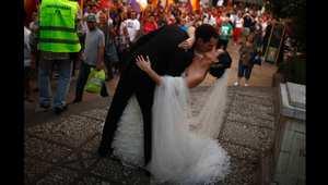 زوجان يتصوران خلال عرسهما في حديقة عامة بإسبانيا شجعتهما مجموعة من المحتجين في مسيرة مناهضة للنظام الملكي على تقبيل بعضهما.