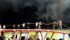 رجال إطفاء وجنود يعملون معا في محاولة لإخماد النيران في مستودع في باري برامانا في الهند.