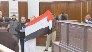 أحد صحفيي الجزيرة يرفع علم مصر أمام المحكمة