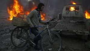 شاب يمشي مع دراجته قرب موقع استدفته غارة جوية في الغوطة