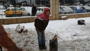 سوريين نازحون من مخيم اليرموك يبحثون عن الدفئ في ظل عاصفة قوية تضرب المنطقة