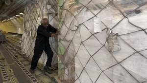 عامل يقوم بتنزيل محتويات إحدى طائرات الإغاثة في مطار صنعاء