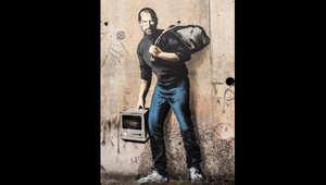 """جدارية جديدة للفنان بانكسي تصور ستيف جوبز """"لاجئاً"""" في مخيم للاجئين السوريين"""