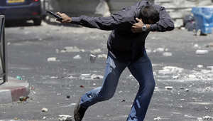 شرطي سري إسرائيلي يشهر سلاحه ويتقي حجارة المتظاهرين الفلسطينيين
