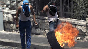 فلسطينيان يشعلان إطارا في القدس