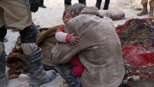 رجل يحتضن طفله بعد قصف لطيران الجيش السوري على حلب الجمعة