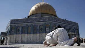 فلسطيني يصلي أمام مسجد قبة الصخرة في الفدس