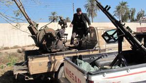 عنصر أمني أمام عربتين صادرتهما القوى الأمنية العراقية