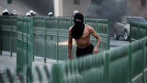 متظاهر يفر من شرطة مكافحة الشغب في البحرين خلال احتجاج في 2013