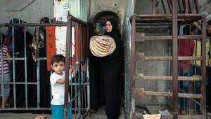 سيدة سرية تشتري الخبز من أحد المخابز في مدينة الرقة