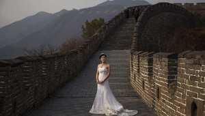 عروس صينية بانتظار التقاط صورة الزفاف في جانب من سور الصين العظيم