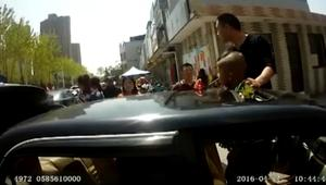 شاهد.. لحظة انقاذ طفل علق في فتحة سقف سيارة والده
