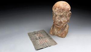 ورقة نقدية عمرها 700 عام في رأس تمثال تاريخي