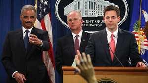المدعي العام الأمريكي(يسار) ايريك هولدر خلال إعلان الاتهام لخمسة ضباط صينيين بالسرقة الالكترونية ، 19 مايو/ أيار 2014