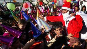 بابا نويل يوزع الهدايا على أطفال عراقيين في مخيم للاجئين شرق أربيل