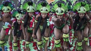 ممثلون يرتدون زي سكان الأمازون الأصليين يحتفلون في وسط المدينة التي ستقام فيها مباراة إيطاليا وانجلترا ضمن بطولة كأس العالم