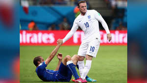واين روني من إنغلترا يساعد جورجيو تشيليني على النهوض خلال المباراة.