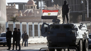 شرطي يقف على آلية أمام أكاديمية الشرطة في القاهرة